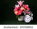 a silver alarm clock and a vase ...   Shutterstock . vector #691968061