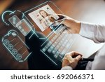 Small photo of Businessman with smartphone communicating with young woman via abstract futuristic screen hologram. Concept of network, communication, family, technology, augmented reality and future