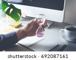 male hand holding hourglass... | Shutterstock . vector #692087161
