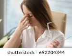 tired woman massaging nose... | Shutterstock . vector #692204344