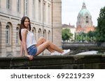 Stock photo young woman posing on bridge in the old town of hannover germany with new city hall landmark 692219239