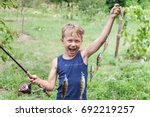 Small photo of Young angler with tackle bass killer, fisherman boy with fish perches caught on spinning with instantaneous reel