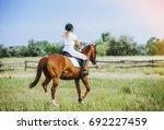 young jockey girl riding a... | Shutterstock . vector #692227459