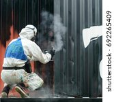 Small photo of man painting with graffiti aerosol can, outdoors. Process of painting