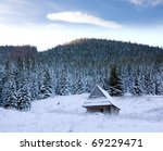 Winter scene in mountains with wooden house - stock photo