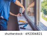 man in a blue shirt does window ...   Shutterstock . vector #692306821