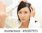 woman looking unhappy with her... | Shutterstock . vector #692307571