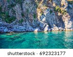 turquoise water and rocky shore | Shutterstock . vector #692323177