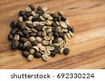 coffee beans on wooden table | Shutterstock . vector #692330224