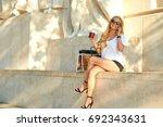 a beautiful young woman sitting ... | Shutterstock . vector #692343631