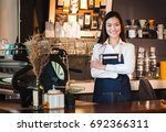 Small photo of Asian female barista wear jean apron crossed her arms at counter bar with smile face, cafe service concept, owner business start up.
