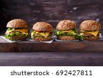 four homemade hamburgers on... | Shutterstock . vector #692427811