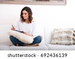 a beautiful young woman siting... | Shutterstock . vector #692436139