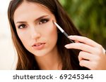 portrait of beautiful  brunette girl making up - stock photo
