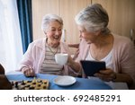 happy senior friends talking... | Shutterstock . vector #692485291
