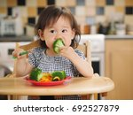 baby girl eating  vegetable at... | Shutterstock . vector #692527879