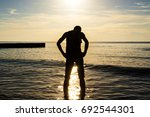 silhouette of a man in the sea... | Shutterstock . vector #692544301