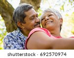senior couple sitting in garden ... | Shutterstock . vector #692570974