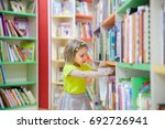 preschooler choosing books at ... | Shutterstock . vector #692726941