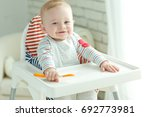 a woman is feeding a child | Shutterstock . vector #692773981