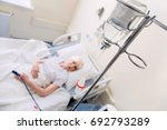 Small photo of Aged ailing woman receiving medication through a drip