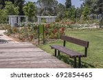Stock photo bench on a promenade between the gardens of the wohl rose park in the modern city of jerusalem 692854465