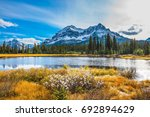 pine trees reflected in smooth... | Shutterstock . vector #692894629