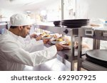 chefs passing ready food to... | Shutterstock . vector #692907925