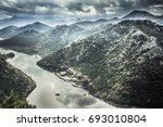 Mountains landscape around Rijeka Crnojevica river curve from high view in overcast day with dramatic sky in Europe country Montenegro