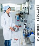 Small photo of young professional woman in uniform checking wine acidity and sugar saturation in chemical laboratory on winery