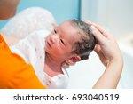 asian newborn baby boy taking a ... | Shutterstock . vector #693040519