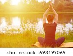 young girl practices yoga on... | Shutterstock . vector #693199069