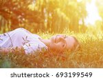 a young girl lying on the grass ... | Shutterstock . vector #693199549