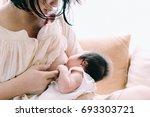 mother breastfeeding her... | Shutterstock . vector #693303721