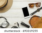 Small photo of Top view or Flat lay the accessories to travel with women / lady or female clothing handbag and hat also sunglasses with item technology.Essential items for traveler mobile phone on table background.