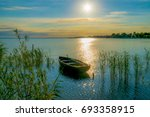 rowing boat on lake at sunset... | Shutterstock . vector #693358915