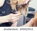 a hairdresser making a haircut | Shutterstock . vector #693423511