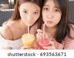 two girls drinking juice | Shutterstock . vector #693563671