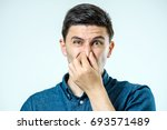 man holding his nose against a... | Shutterstock . vector #693571489