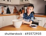 kid boy preparing dough for... | Shutterstock . vector #693572935