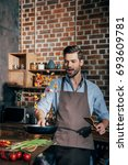 handsome excited man with apron ... | Shutterstock . vector #693609781
