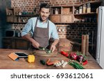 handsome young man cutting... | Shutterstock . vector #693612061