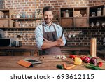 handsome young man with knife... | Shutterstock . vector #693612115