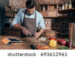 handsome young man cutting... | Shutterstock . vector #693612961