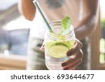 woman holding glass of infused... | Shutterstock . vector #693644677