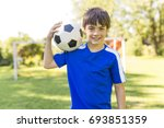 a young boy with soccer ball on ... | Shutterstock . vector #693851359