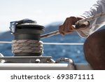 mans hand pulling winch rope on ... | Shutterstock . vector #693871111