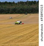 """Small photo of Chortkiv - Ternopil - Ukraine - August 4, 2017. The grain harvesters in the field collect the ripe wheat harvest on the fields of the agro enterprise """"Berezina"""""""