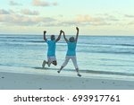 senior couple jumping on... | Shutterstock . vector #693917761
