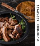Small photo of Cooked meat ribs in plate with a spicy sauce marinade with honey and herbs on dark wooden background. Top side view.